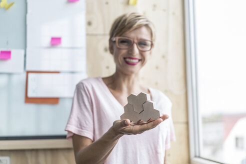 Woman holding wooden building blocks in modern office - RIBF00654