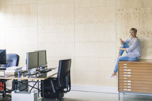 Smiling businesswoman sitting on filing cabinet in creative office - RIBF00666