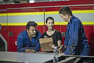 Mechanics working at fire brigade workshop reading check list - ZEF11695