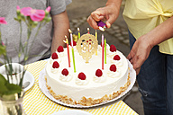 Hand lighting candles on 80th birtday cake - MFRF00766
