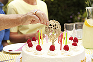 Hand removimg 80th birthday decoration from cake - MFRF00772