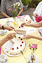 Hands putting cream cake on plates - MFRF00775