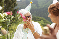 Senior ladies laughing at celebration, wearing party hats - MFRF00778
