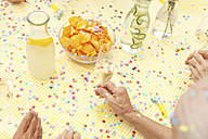 Celebrating senior sitting at table with infused water, champagne and potato chips - MFRF00784