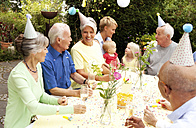 Extended family and friends having birthday party in garden - MFRF00790