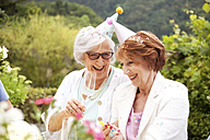 Senior ladies drinking champagne at birthday party - MFRF00796