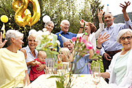 Extended family and friends having birthday party in garden - MFRF00811