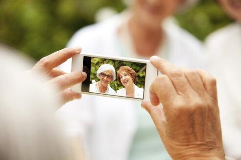 Man taking selfie of two senior women - MFRF00823