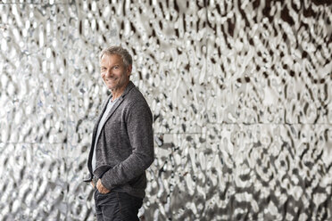 Confident businessman in front of rippled wall - PESF00355
