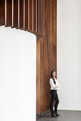 Confident businesswoman standing at wooden wall - PESF00373
