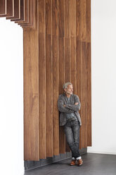 Confident businessman leaning against a wooden wall - PESF00379