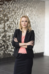 Portrait of confident businesswoman in front of rippled wall - PESF00382