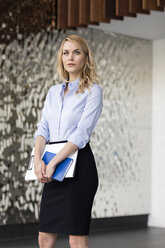 Confident businesswoman holding folder - PESF00385