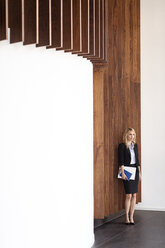 Businesswoman at wooden wall holding folders - PESF00391