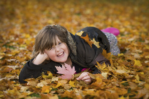 Laughing girl lying on soil covered with autumn leaves - MJOF01317
