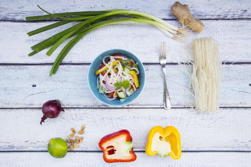 Bowl of glass noodle salad with vegetables and ingredients on wood - LVF05610