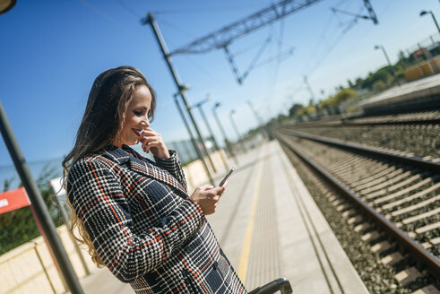 Smiling woman on platform looking at cell phone - KIJF00863
