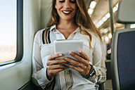 Smiling woman on a train using a tablet - KIJF00872