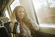 Woman on a train listening to music with headphones - KIJF00875