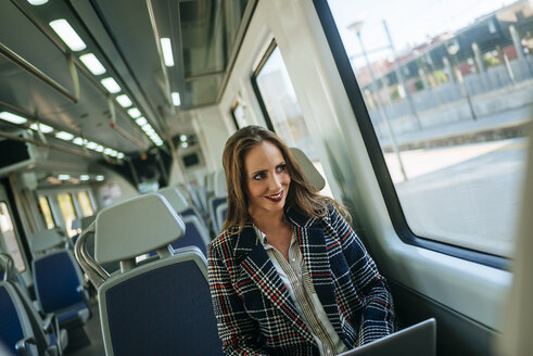Businesswoman on a train using a laptop - KIJF00878