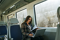 Businesswoman on a train with notebook and laptop - KIJF00881