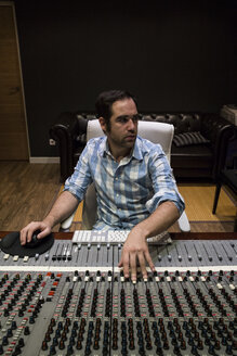 Man working in the control room of a recording studio - ABZF01529