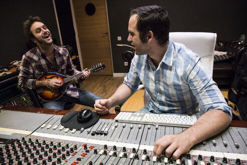 Guitar player and audio engineer in a recording studio - ABZF01535