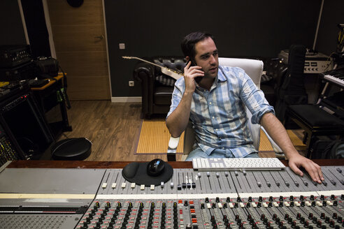 Man in the control room of a recording studio talking on cell phone - ABZF01538