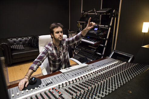 Man working in the control room of a recording studio raising his hand - ABZF01547