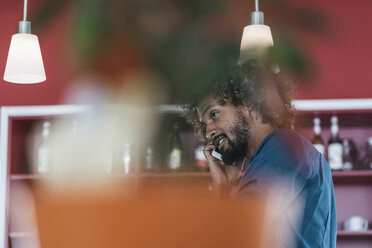 Young man in coffee shop using mobile phone - JOSF00412