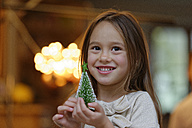 Portrait of smiling little girl with miniature Christmas tree - LBF01512
