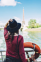 France, Paris, back view of woman on tour boat looking at Eiffel Tower - GEMF01262
