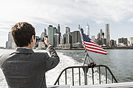 USA, Brooklyn, back view of businesswoman on a boat taking picture of Manhattan skyline - UUF09248