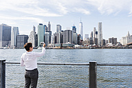 USA, Brooklyn, businesswoman taking picture of Manhattan skyline - UUF09251