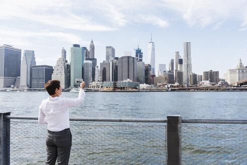 USA, Brooklyn, businesswoman taking picture of Manhattan skyline - UUF09251