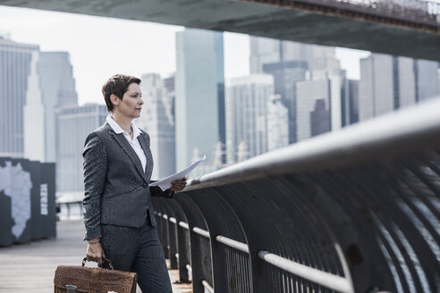 USA, Brooklyn, businesswoman standing in front of Manhattan skyline - UUF09260