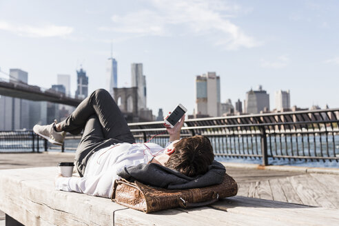 USA, Brooklyn, businesswoman lying on bench listening music with earphones - UUF09263