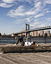 USA, Brooklyn, businesswoman lying on bench listening music with earphones - UUF09266