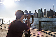 USA, Brooklyn, woman looking at Manhattan skyline with coin operated binoculars - UUF09272