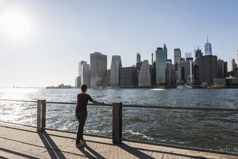 USA, Brooklyn, back view of woman  looking at Manhattan skyline - UUF09275