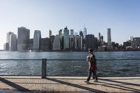 USA, Brooklyn, businesswoman looking at her smartphone in front of Manhattan skyline - UUF09278