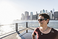 USA, Brooklyn, portrait of smiling woman wearing sunglasses in front of Manhattan skyline - UUF09281