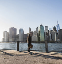 USA, Brooklyn, back view of businessman with briefcase standing in front of Manhattan skyline - UUF09284