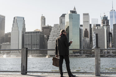 USA, Brooklyn, businessman with briefcase and smartphone standing in front of Manhattan skyline - UUF09287