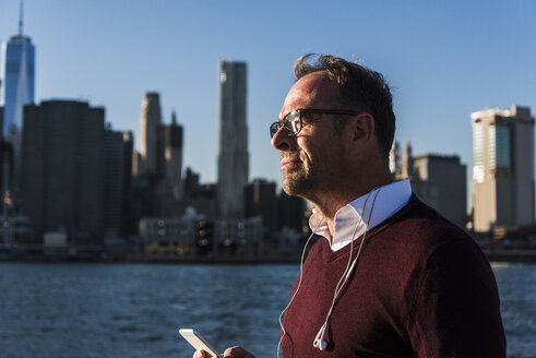 USA, Brooklyn, businessman with smartphone and earphones at sunlight - UUF09293