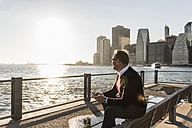 USA, Brooklyn, relaxed man with smartphone sitting on bench looking at view - UUF09296