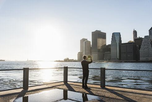 USA, Brooklyn, back view of man taking picture of Manhattan skyline with tablet - UUF09299