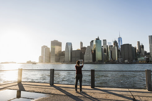 USA, Brooklyn, back view of woman taking picture of Manhattan skyline with tablet - UUF09302