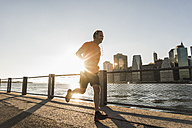 USA, Brooklyn, man jogging in front of Manhattan skyline in the evening - UUF09305