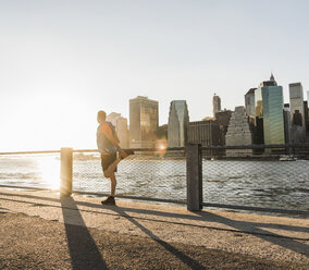 USA, Brooklyn, man doing stretching exercises in front of Manhattan skyline in the evening - UUF09311